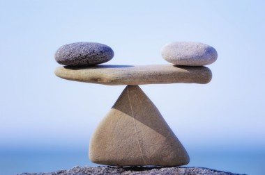 Two round rocks balanced on a flat rock on a triangle rock