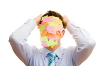 Guy with post-it notes covering his face pulling his hair out